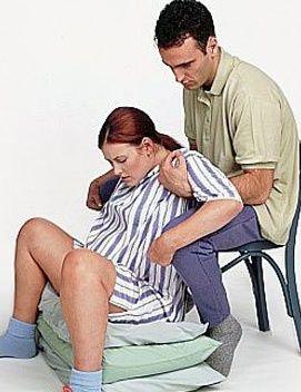 Un om care ajuta o femeie în travaliu