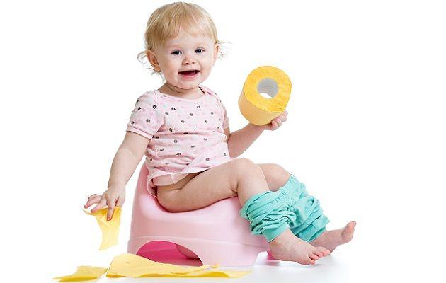 Ребенок сидит на горшке и держит в руках туалетную бумагу