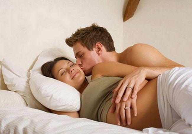 Мужчина с беременной женщиной в постели